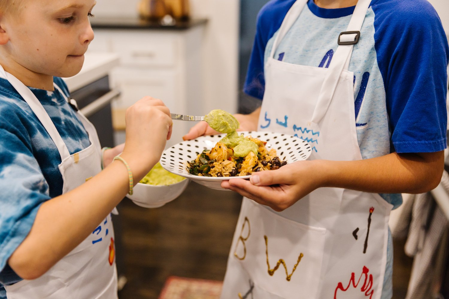 Cooking with kids - Fos plating his black bean and shrimp bowl with guacamole