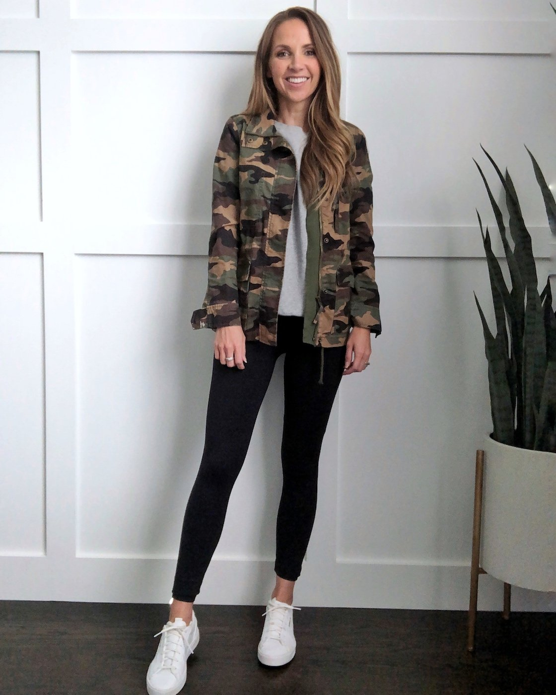 white sneakers in the fall: black leggings and camo jacket