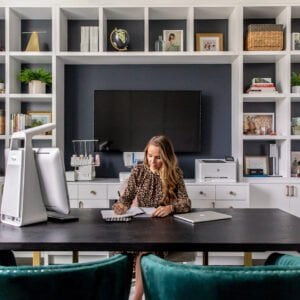 home office with built in white shelves with gray wall