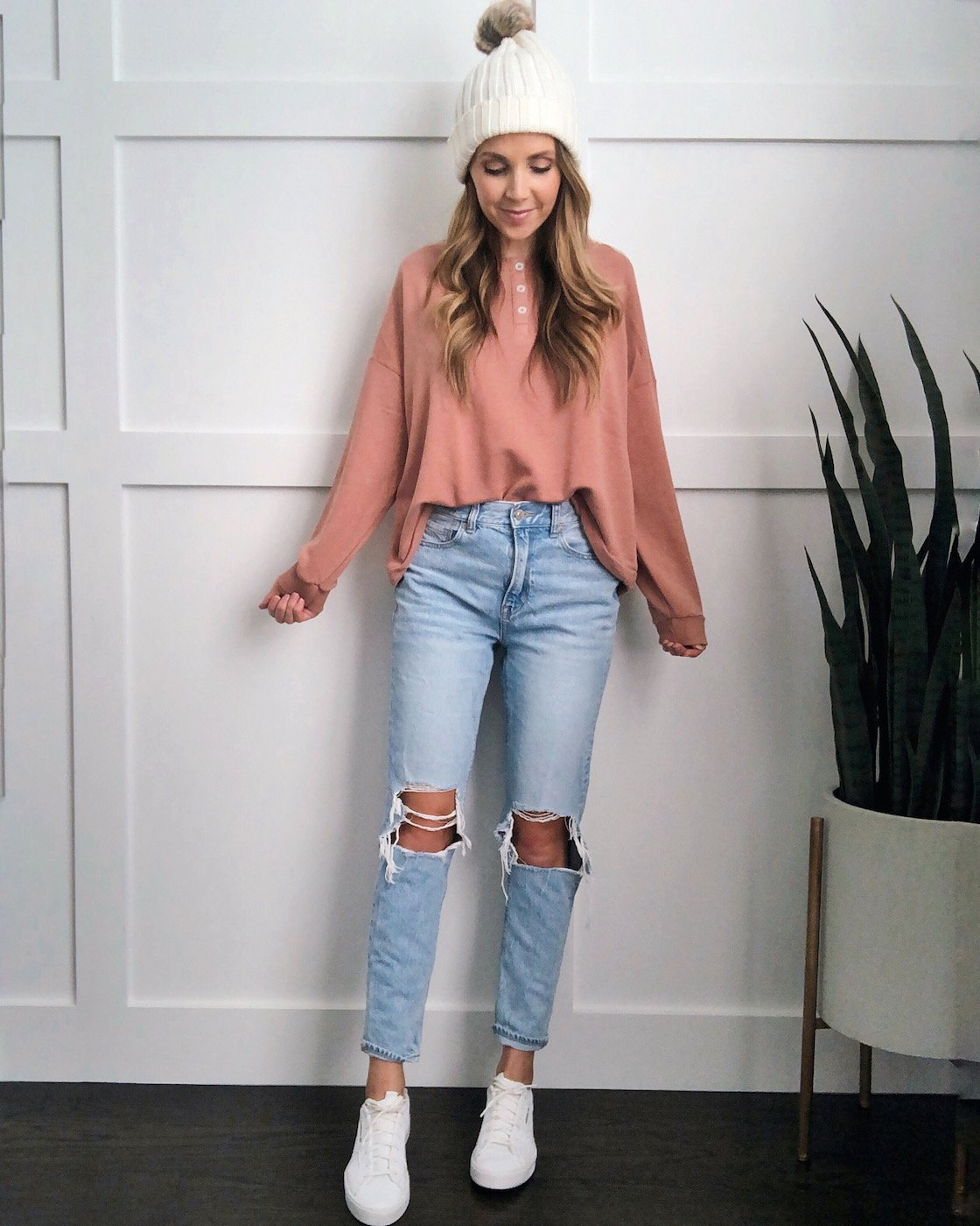 white sneakers in the fall: pink sweatshirt and light wash jeans