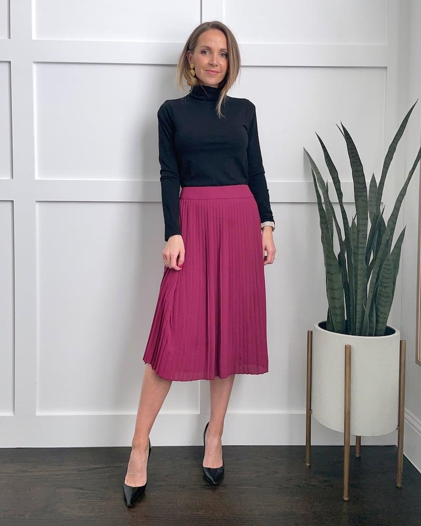 pink pleated midi skirt and black turtleneck