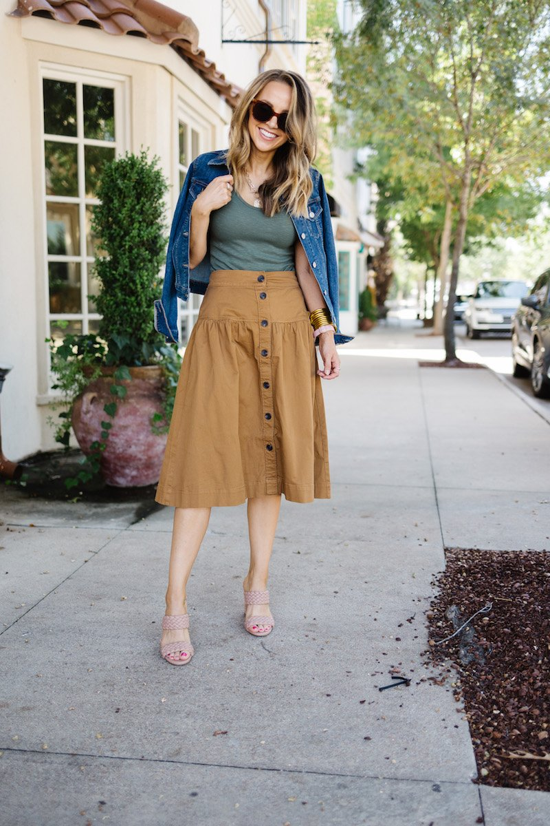 green bodysuit with denim jacket and brown skirt