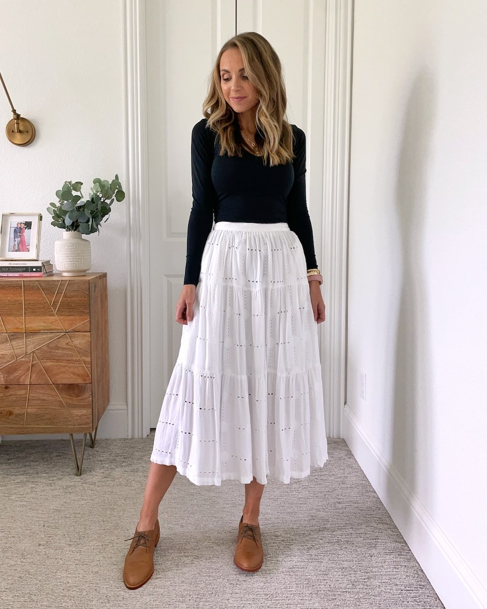 white skirt with black bodysuit and brown oxford shoes